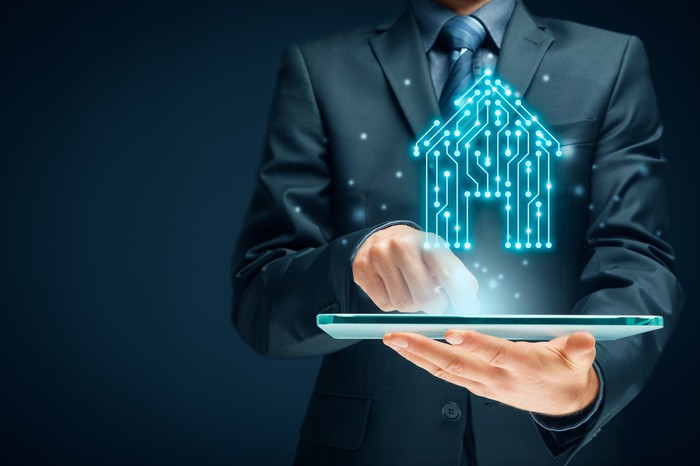 A person is holding a tablet displaying a digital image of a home.