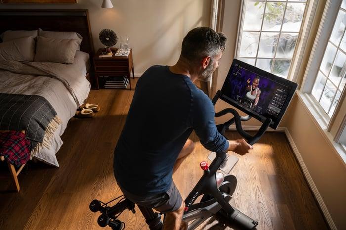 A man uses a Peloton Bike in a bedroom.