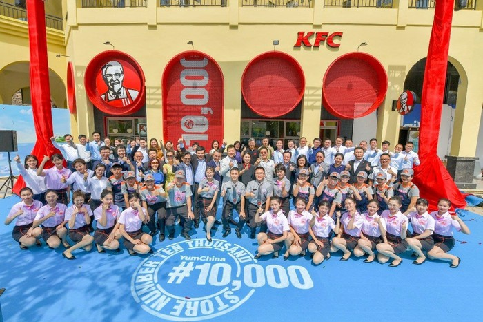 Employees from Yum China's 10,000th KFC store pose in front of the store