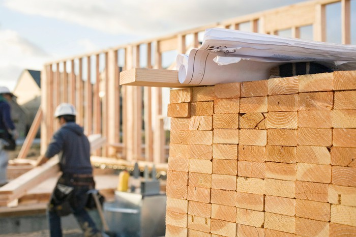 A stack of 2 by 4s at a construction site, with a worker in the background.