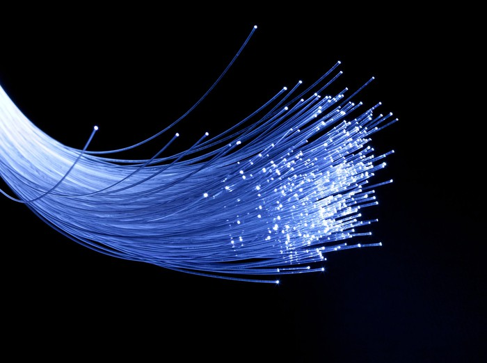 A bundle of fiber-optic cable strands lit up in white against a black background.
