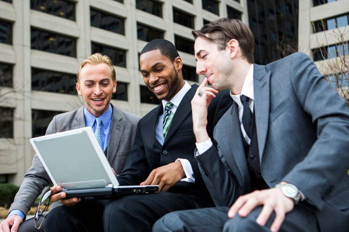 Three friends sitting together looking at one player build a DraftKings roster.