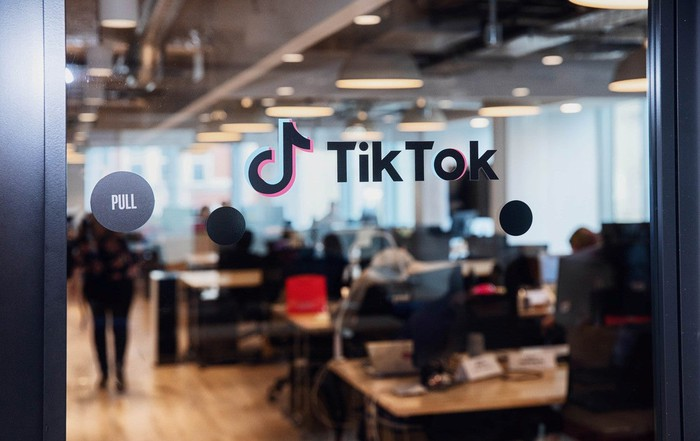 Glass door with TikTok logo on it, and office beyond.