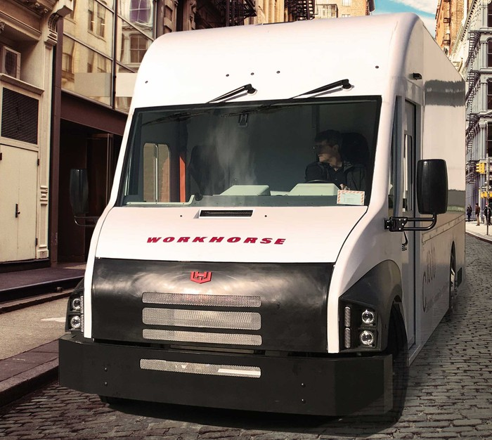 White Workhorse electric van on a cobblestone street with buildings nearby.