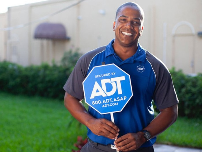 An ADT technician holding a company sign.