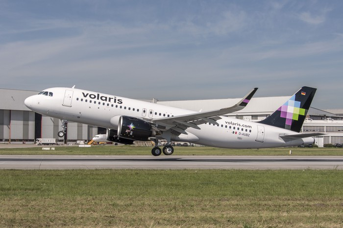A Volaris plane touching down on a runway