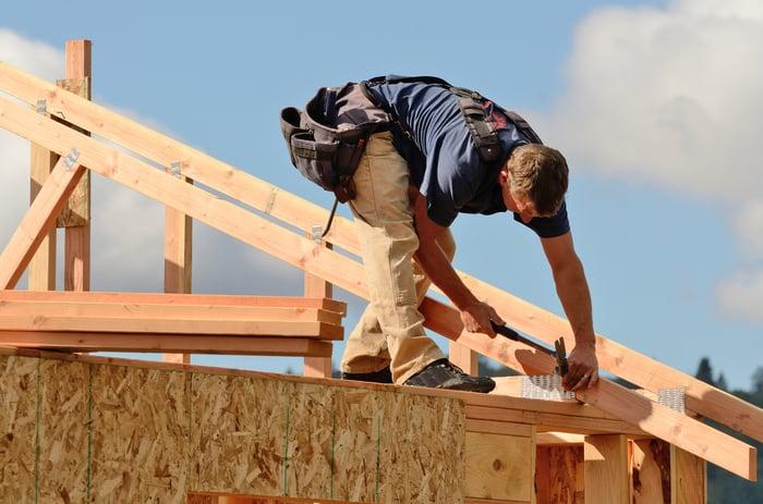 Carpenter installing roof trusses
