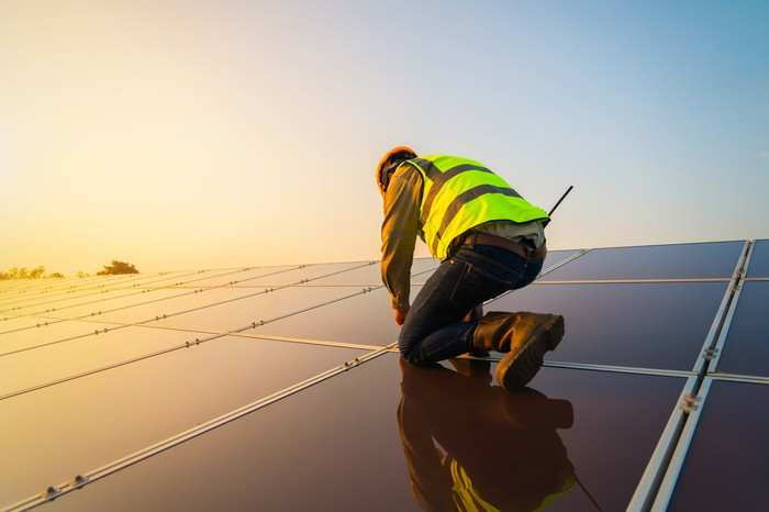 worker on a roof working on solar panels