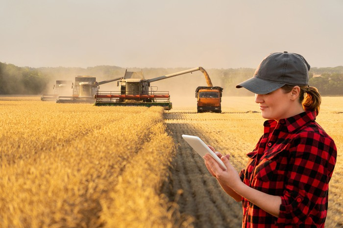 A woman with a notebook in a farm field with farm equipment working in the background