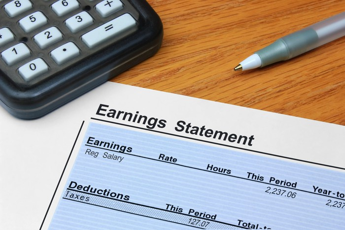 Earnings statement on wooden surface next to calculator and pen