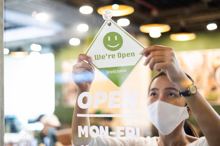 Woman wearing mask hanging Open sign in retail store