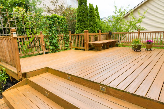 Large outdoor home deck with landscaped trees in the background
