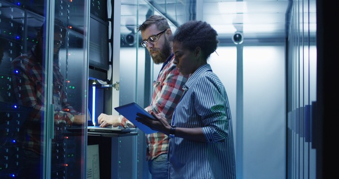 A man and woman working at a computer terminal in a data center