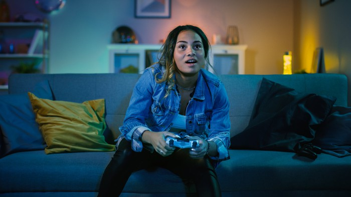 Woman seated on a couch playing a video game.