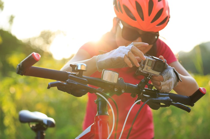 bicyclist looking at action camera mounted on handle bars