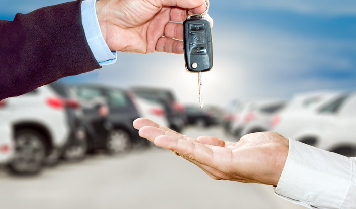 Closeup of one hand giving a new key to a customer's hand with a line of used cars in the background.