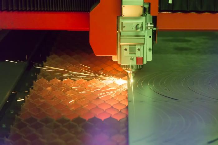 Photo of an industrial  fiber laser cutting through a sheet of plate steel.