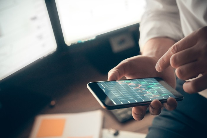 Man holding phone while looking at stock charts.