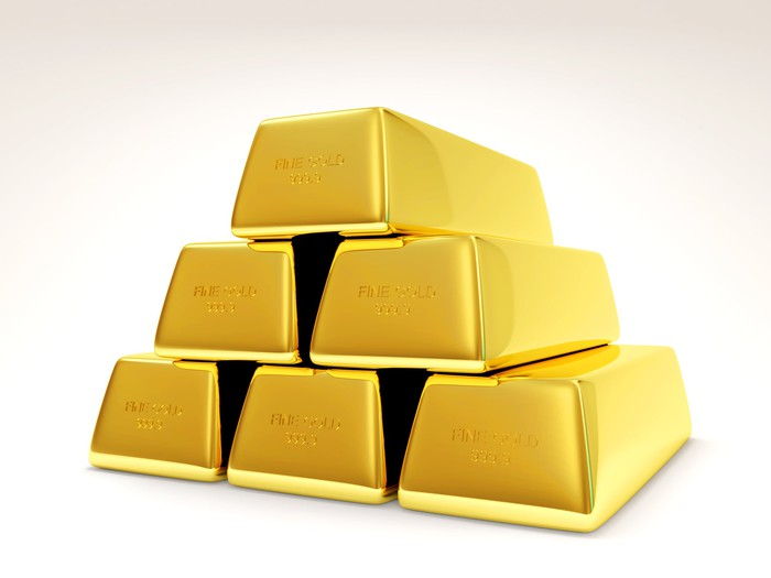 Six bars of gold bullion stacked in a pyramid.
