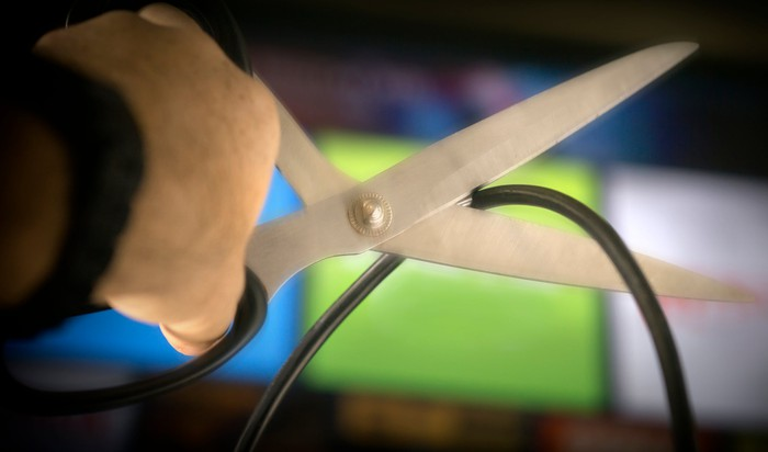 A pair of scissors is about to cut a coaxial cable, held up in front of several blurred TV screens.