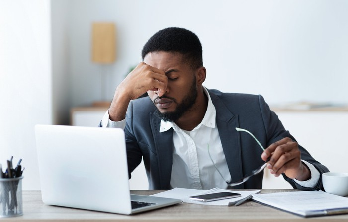 A man closes eyes and takes off glasses at work, conveying strain.