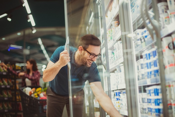 A man reaches into a refrigerator at the grocery store.