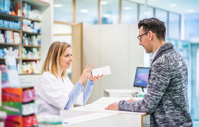 A pharmacist speaks to a customer at pharmacy counter.