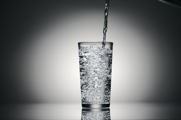 Sparkling water is poured into a tall glass.