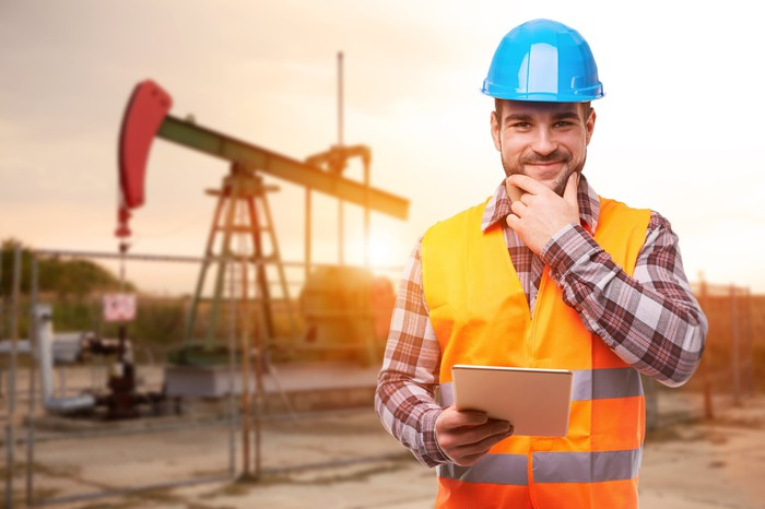A worker standing in front of an oil rig with tablet in his hand