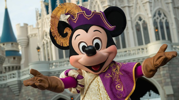 Mickey Mouse in a regal prince costume in front of the Disney World Magic Kingdom castle.
