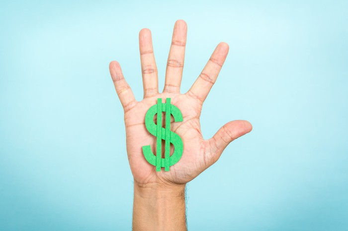 A hand has five fingers stretched out, with a green dollar sign on the palm.