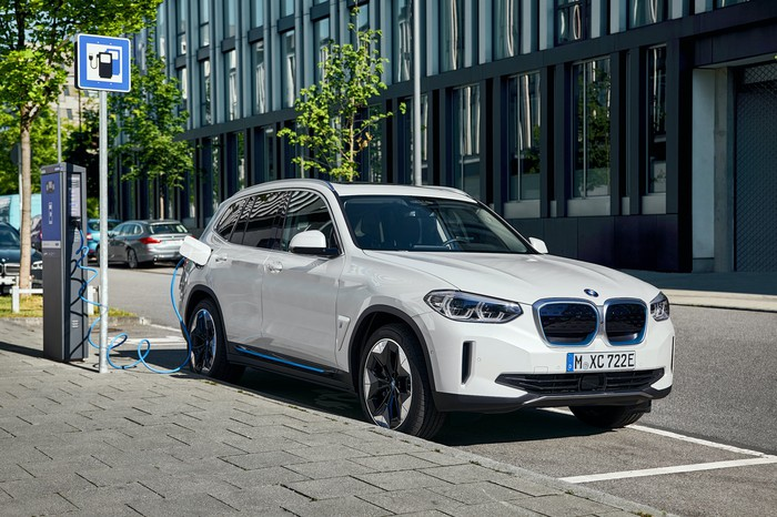 A white BMW iX3, a compact electric crossover SUV, at a roadside charging station