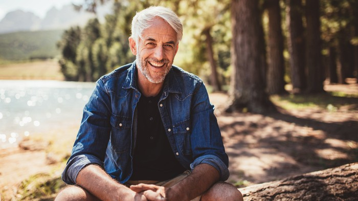Smiling older man sitting outdoors on top of a tree trunk.