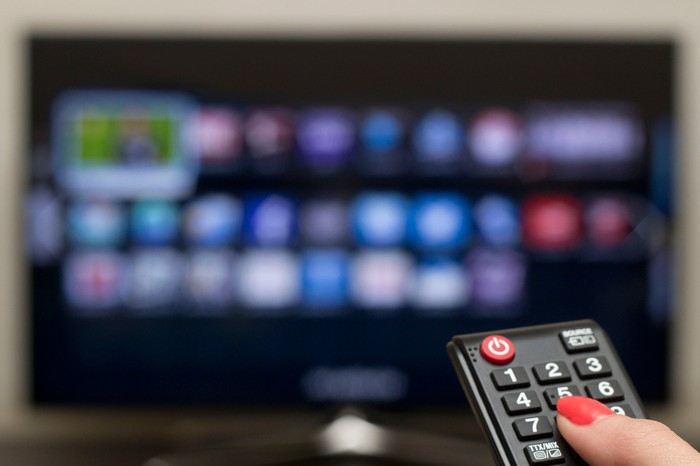 Woman pointing a remote control at a TV showing streaming channel options.