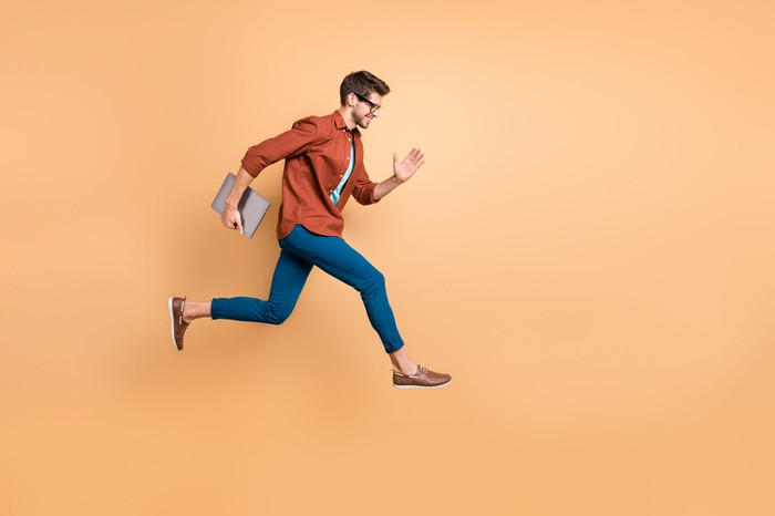 A young man carries a laptop and runs  in mid air against a beige background.