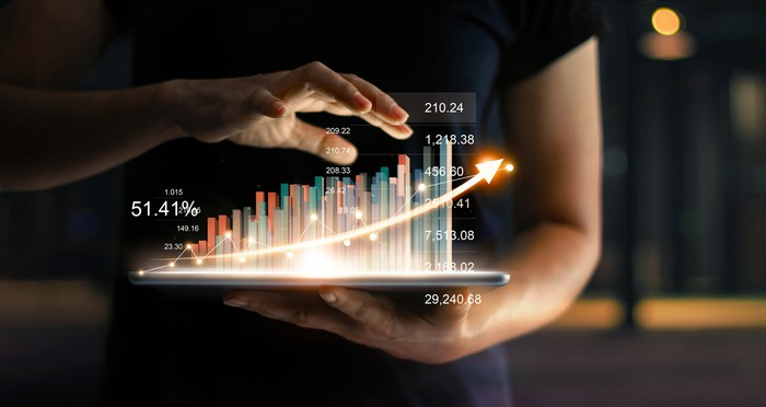 Person holds glowing tablet with rising financial chart above it