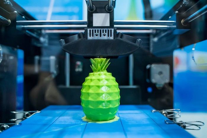 Close-up of a 3D printer printing a green plastic pineapple.