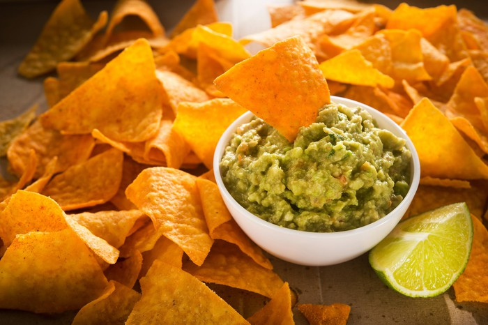 Corn chips scattered around a bowl of guacamole
