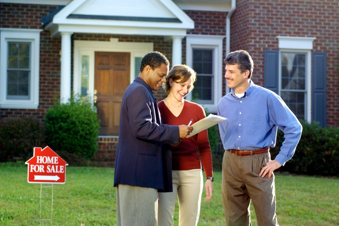 Three people in front of a house with a for sale sign on the lawn