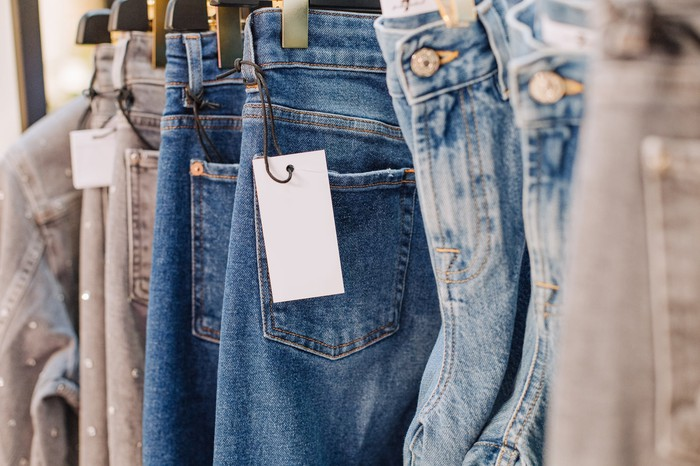 Various styles of blue jeans hang on a sale rack.