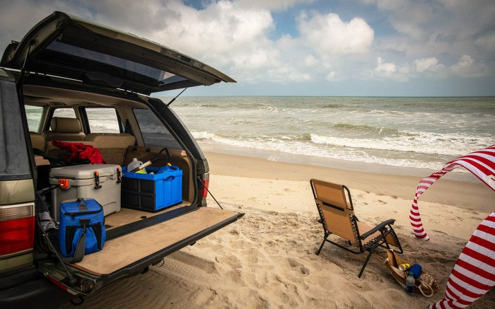 High-end coolers rest on a car's tailgate on a beach.