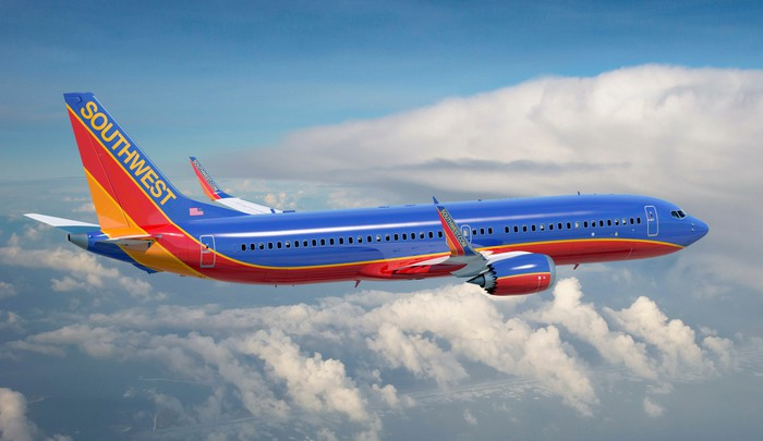 A Boeing 737 MAX airliner in Southwest Airline's trade dress, shown in flight above clouds.