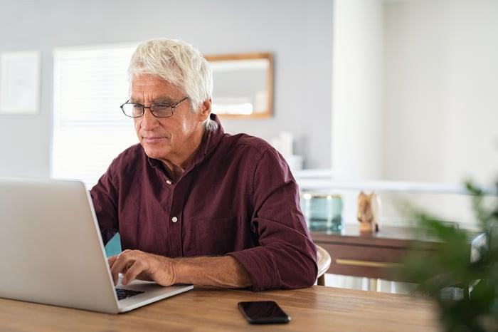 Older man typing on laptop