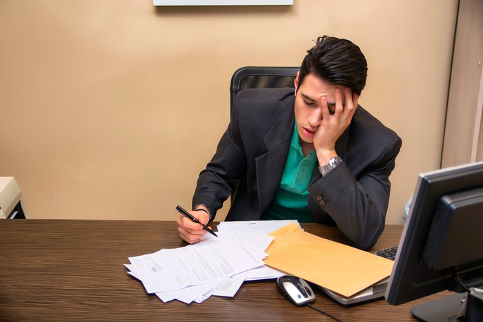 Man at desk holding his head with papers spread out in front of him