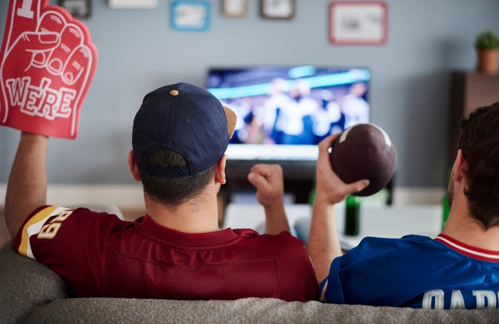 Two sports fans watching a football game on TV from their couch.