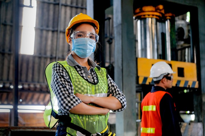 A woman in a hard hat, work vest, and mask stands in an industrial building.