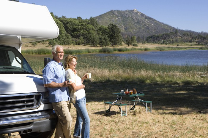 A couple standing in front of their RV are enjoying the outdoors.