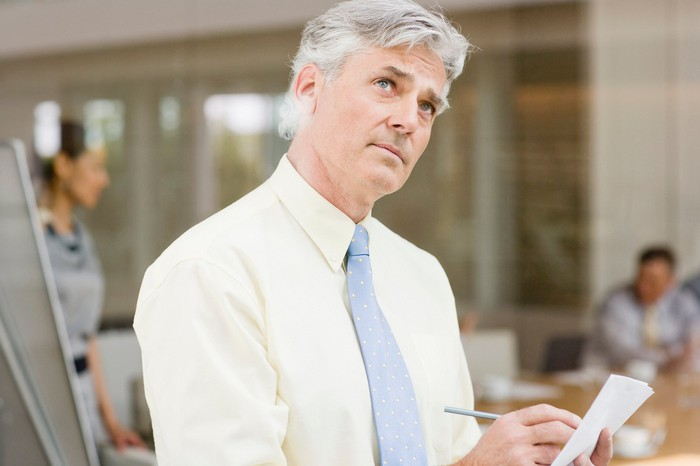 Older man in dress shirt and tie writing on piece of paper