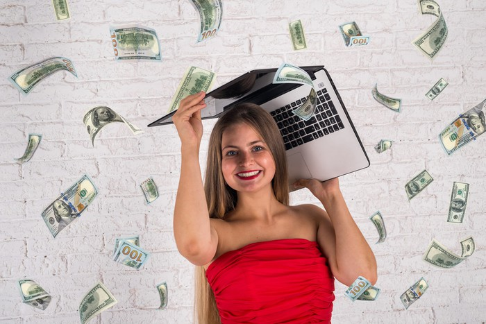 $100 bills raining down on a woman holding a laptop over her head