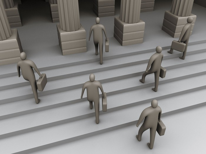 Digitally illustrated human figures carrying briefcases and marching up courthouse steps.